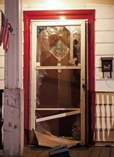 The smashed front door of the house.
